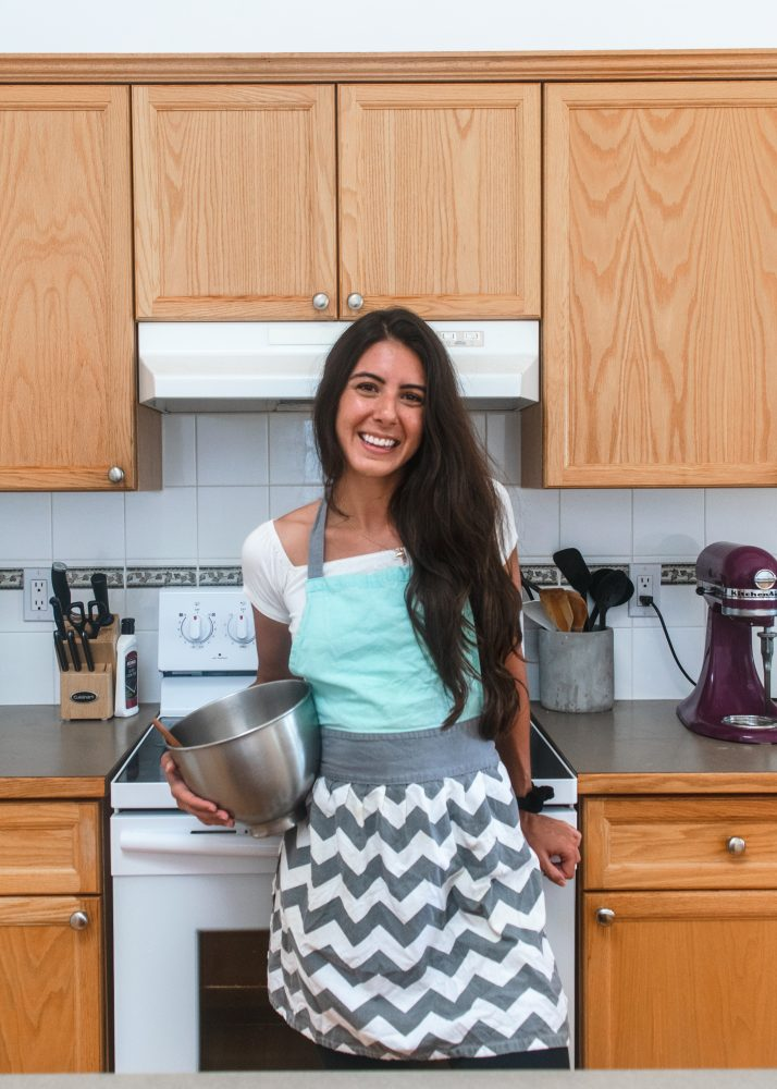 Photo of a girl in the kitchen wearing an apron and holding a mixing bowl
