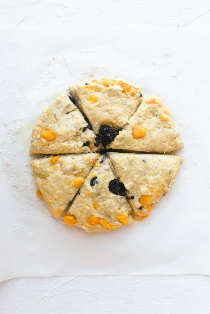 Round scone dough on a floured surface, cut into triangle pieces