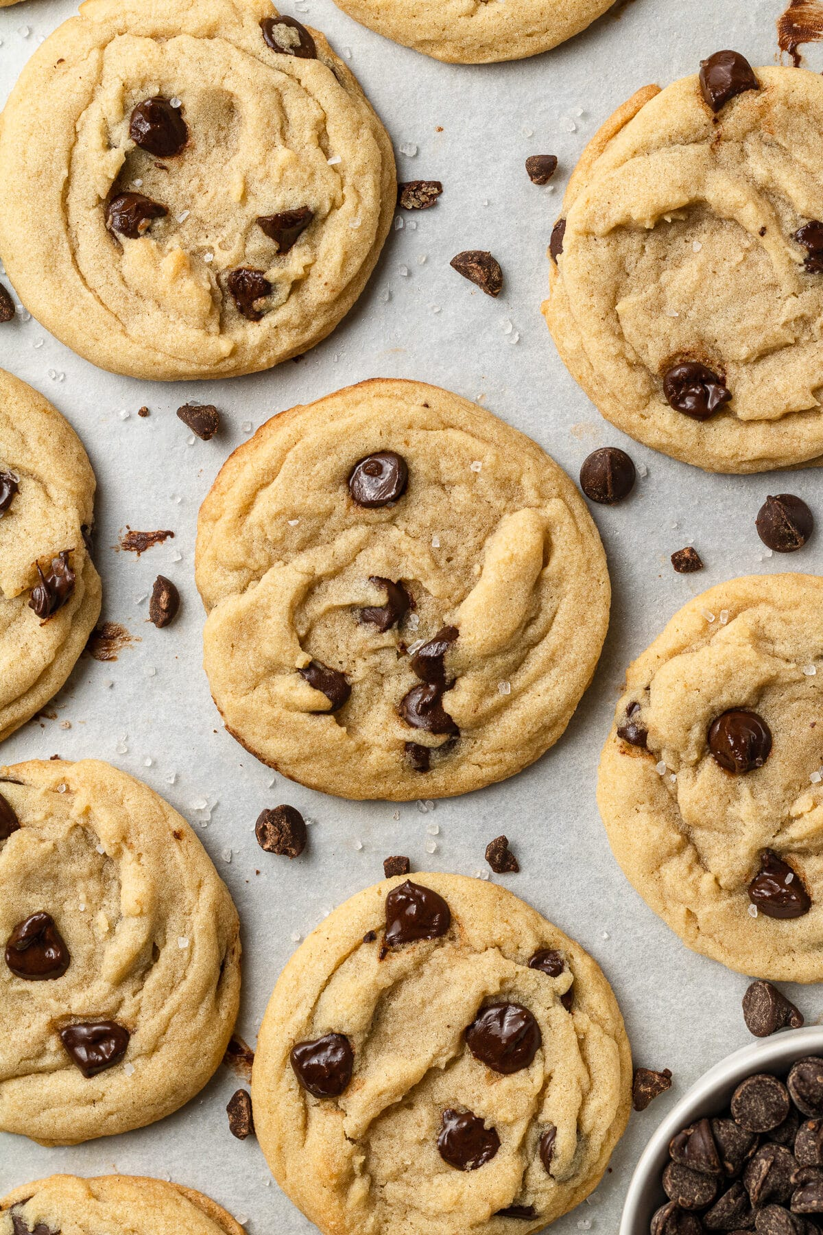 dairy free chocolate chip cookies on a baking sheet with chocolate chips scattered around