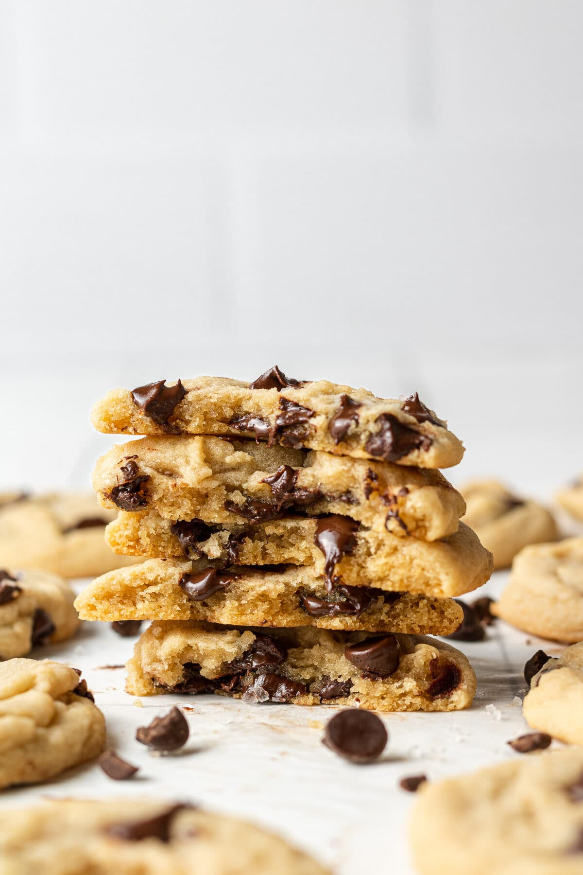 dairy free chocolate chip cookies split in half and stacked on top of each other with more cookies around them