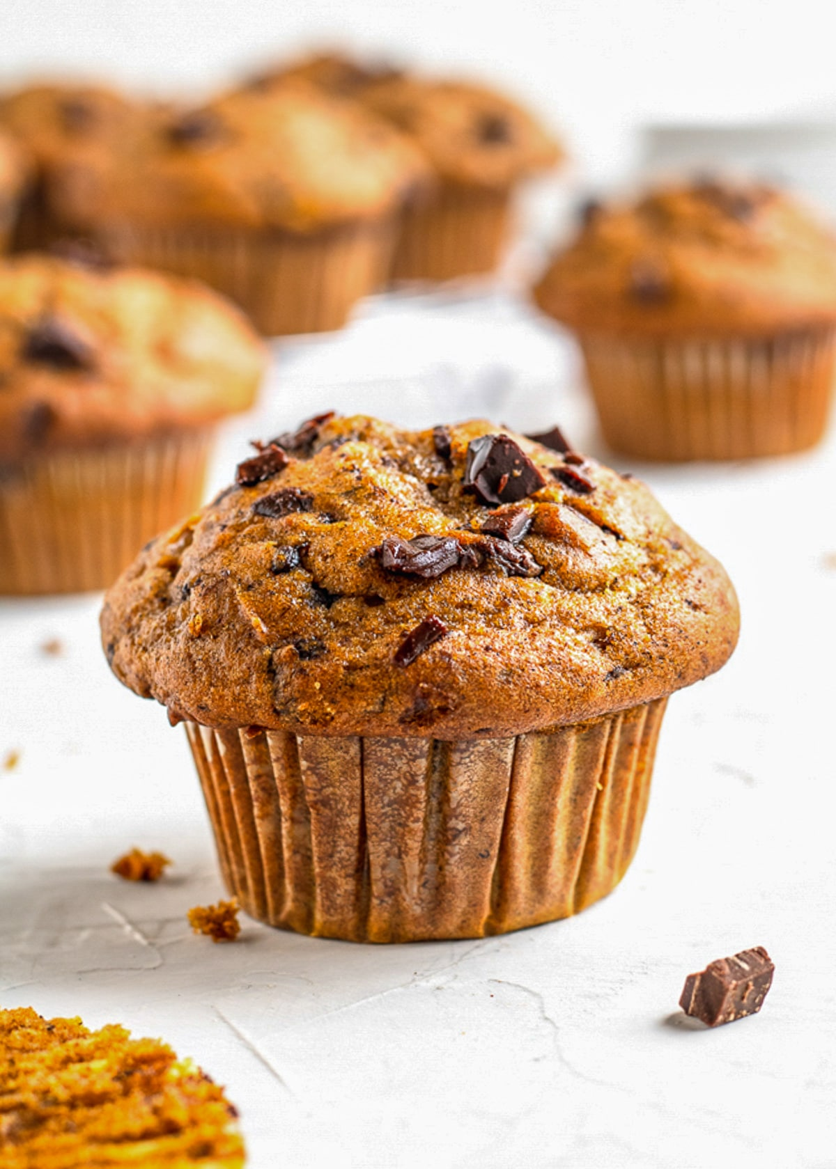 pumpkin banana muffin with more muffins in the background and chocolate scattered around them