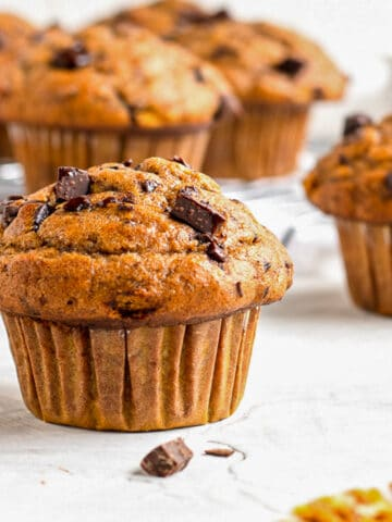pumpkin banana muffin with more muffins in the background on a cooling rack
