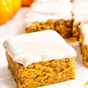 slice of pumpkin sheet cake with more cake in the background