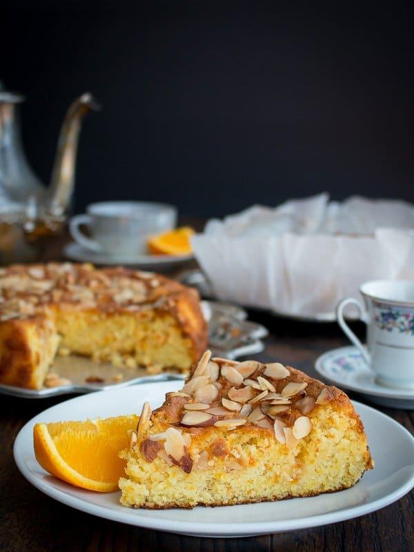 a slice of orange almond flourless cake with an orange slice beside it