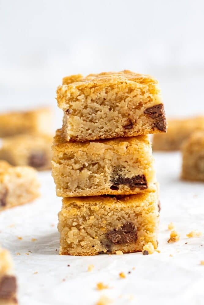 three chocolate chunk blondies stacked on top of eachother