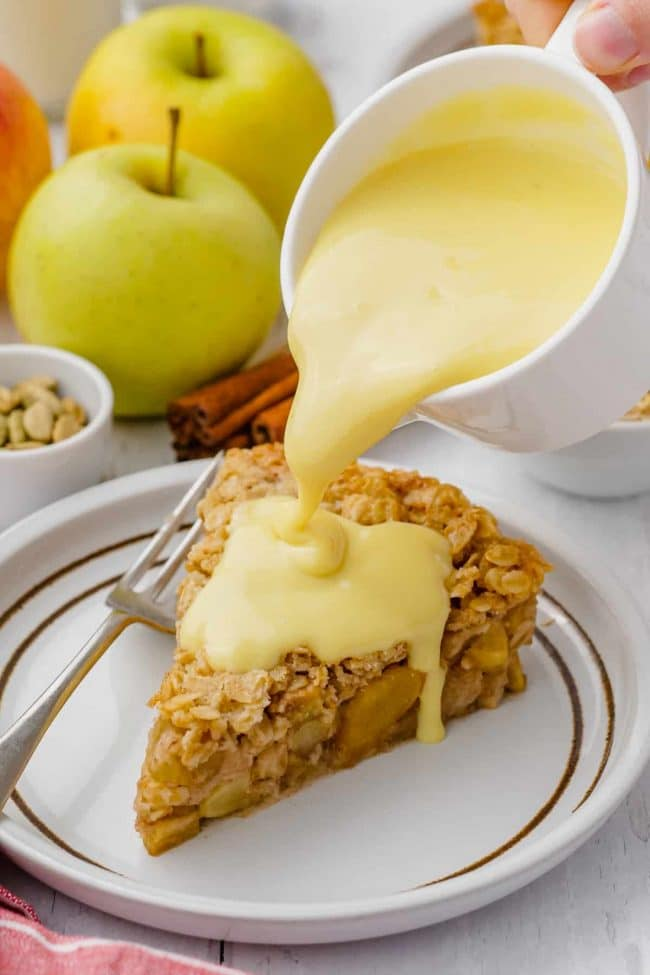 a piece of apple pie with custard being poured over it