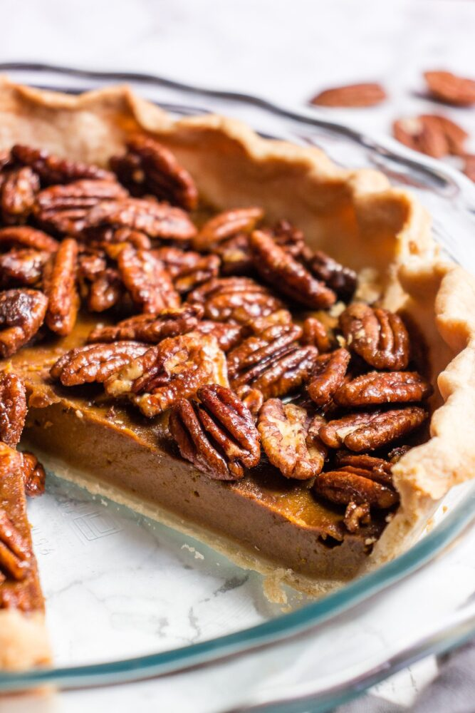 vegan pumpkin pecan pie with a slice out of it