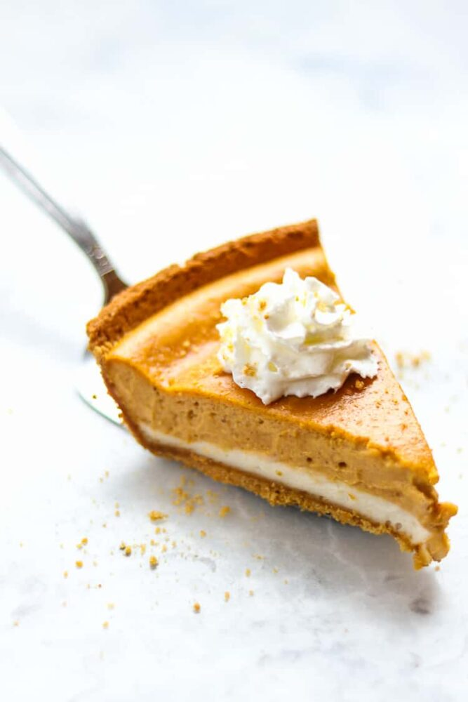 a slice of layered pumpkin cheesecake with dairy free whipped cream on top