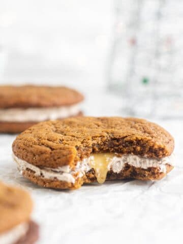 ginger sandwich cookie with a bite out of it and spiced buttercream inside