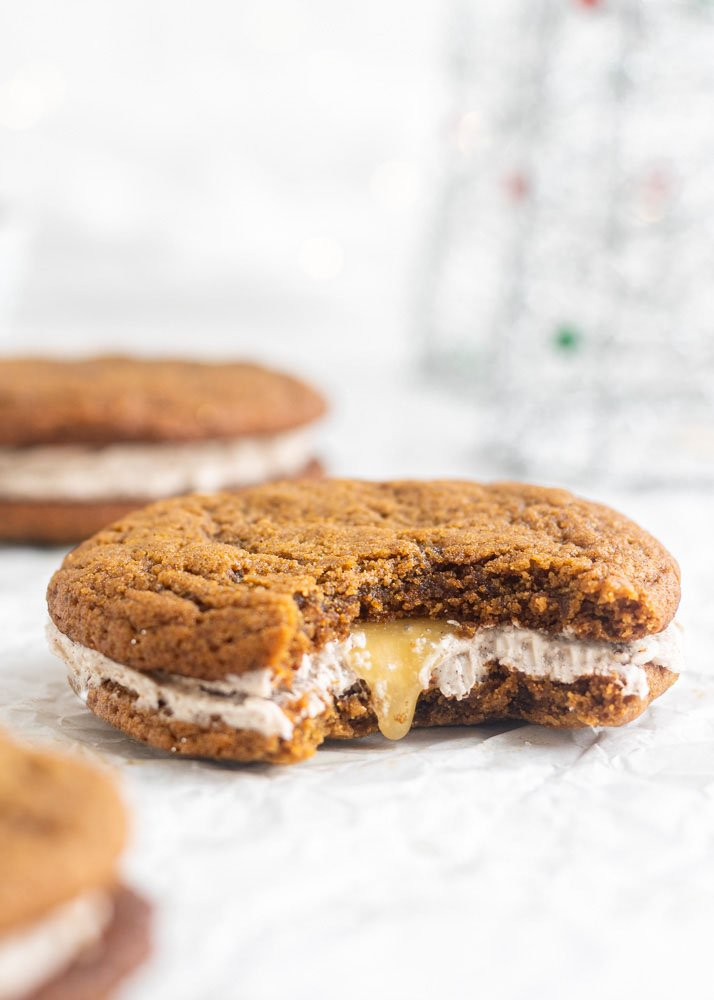 a ginger sandwich cookie with a bite out of it and spiced buttercream inside