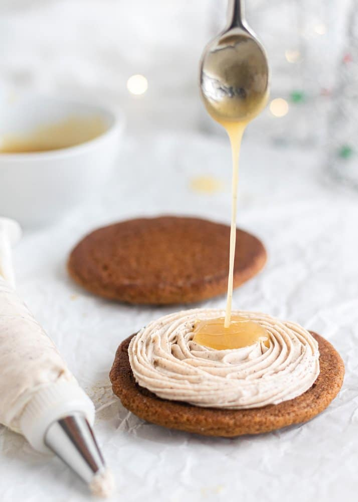 gingerbread cookie with spiced buttercream and caramel being poured in the middle
