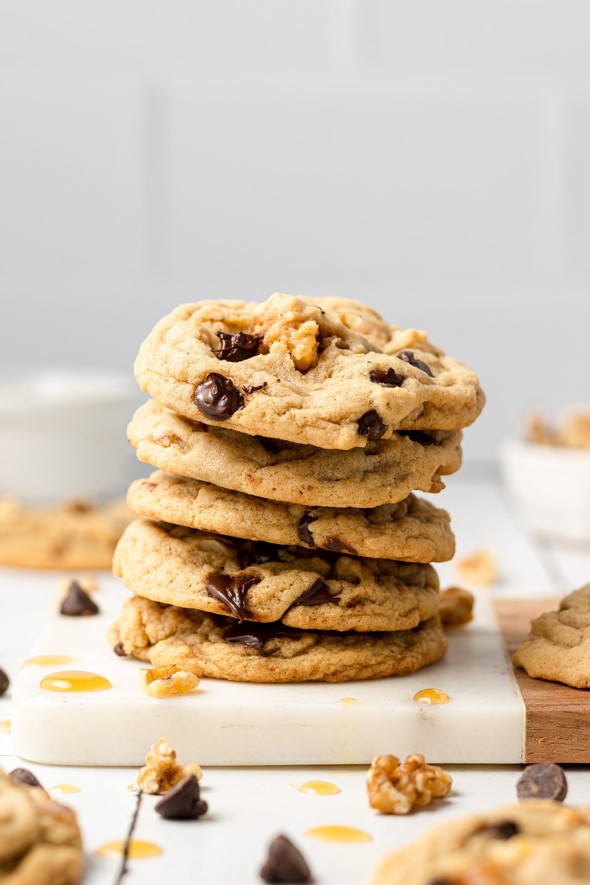 maple chocolate chip cookies stacked with maple syrup drizzled on top