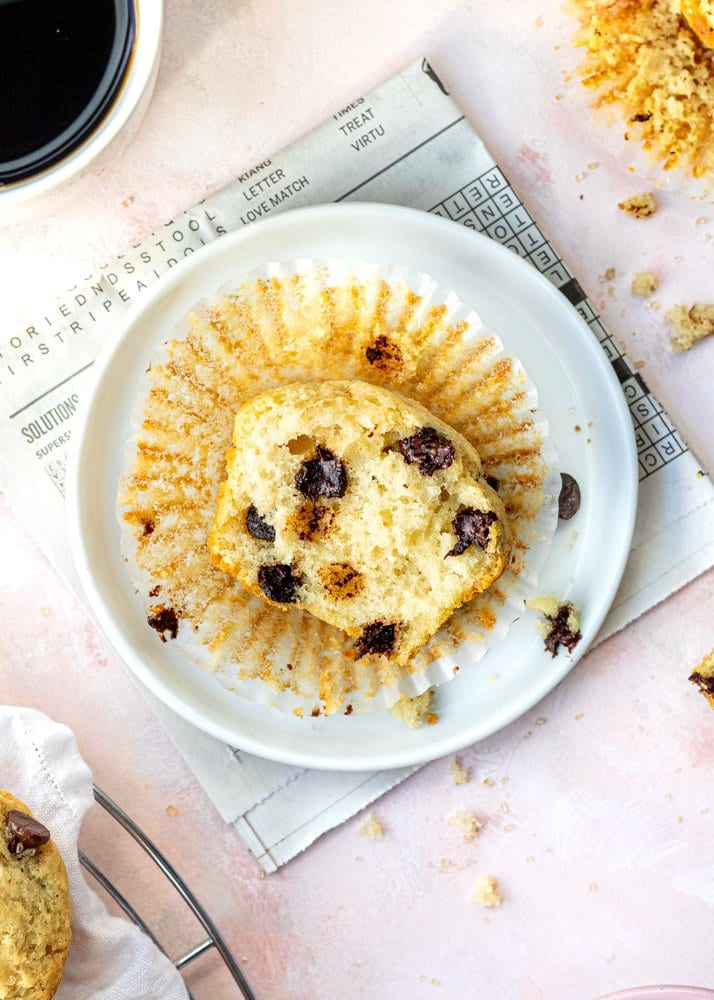 overhead shot of half of a chocolate chip muffin on a plate with a cup of coffee and newspaper underneath