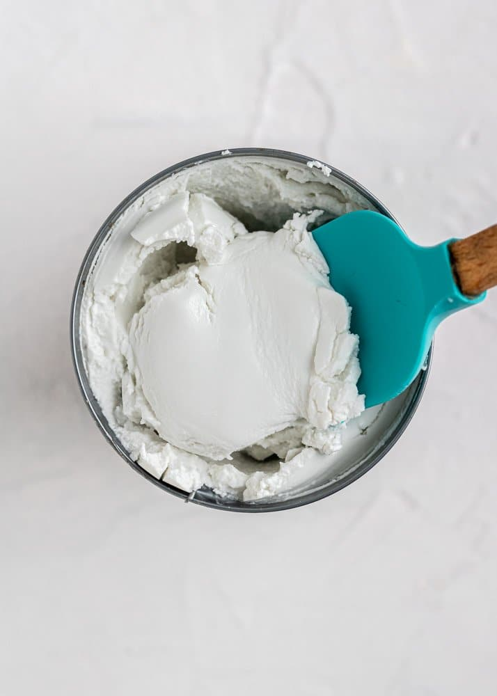 canned coconut milk with hardened cream being scooped out