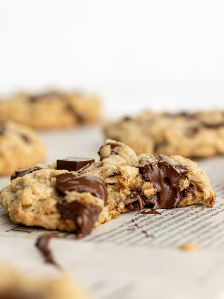 a dairy free oatmeal cookie with a bite out of it and other cookies behind it