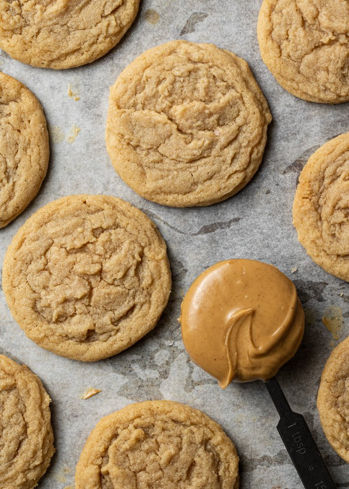 dairy free peanut butter cookies on a baking sheet with a spoon of peanut butter