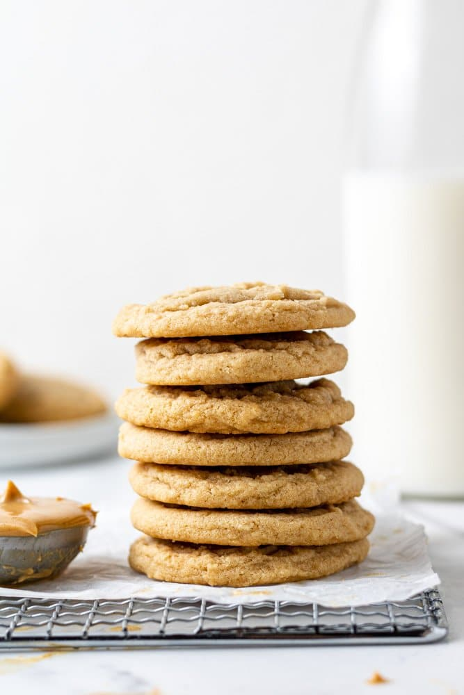 dairy free peanut butter cookies stacked with milk in the background