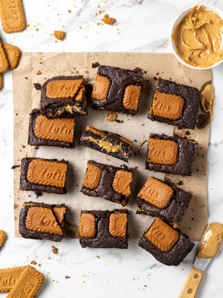 biscoff brownies sliced on parchment with cookies scattered around them