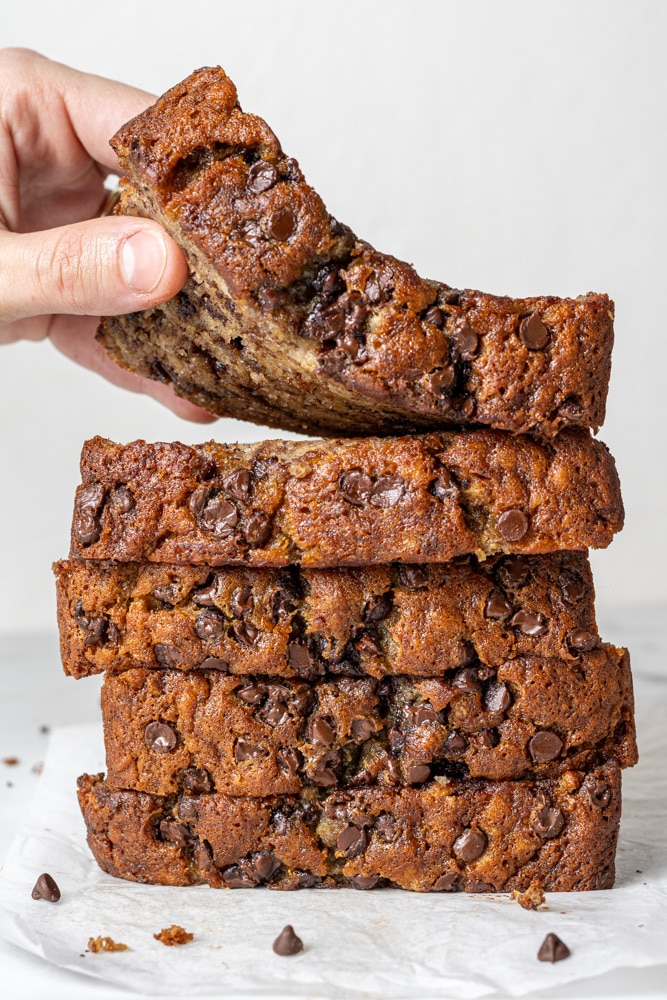 a hand grabbing a slice of banana bread from a stack