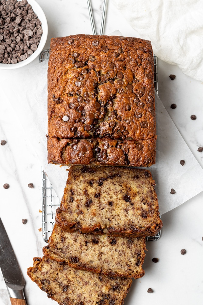 a loaf of dairy free banana bread from above sliced with mini chocolate chips scattered around it