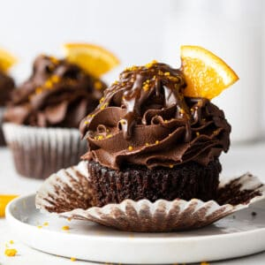 a chocolate orange cupcake on a plate with orange slices scattered around it