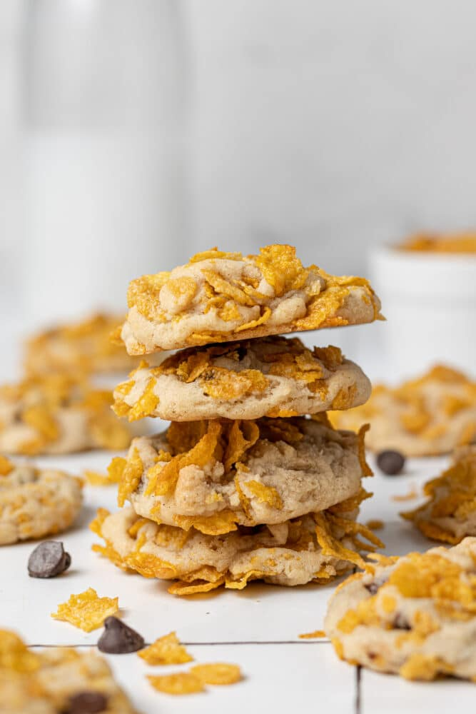 corn flakes cookies stacked on each other with more biscuits scattered around