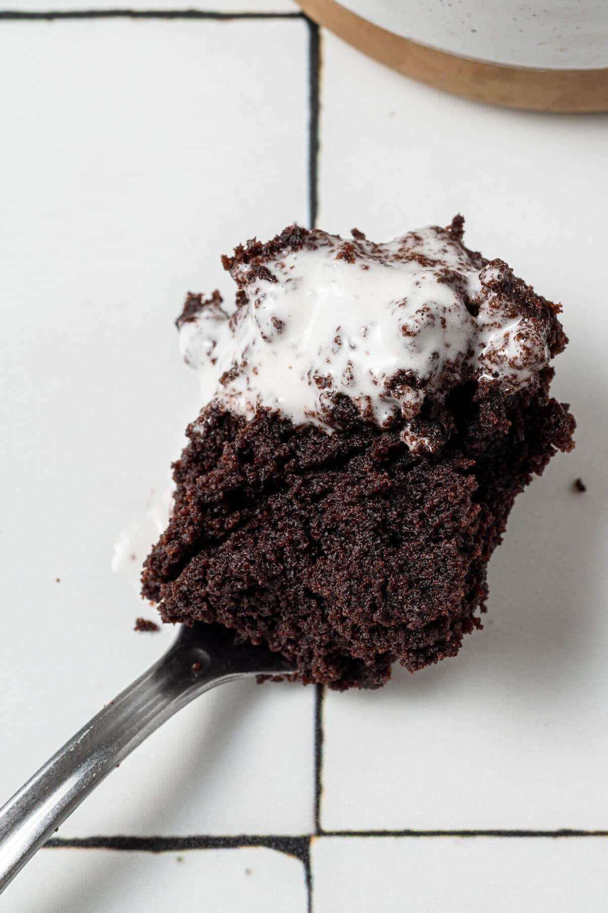 a spoon with a chocolate vegan mug cake on it with whipped cream melting on top