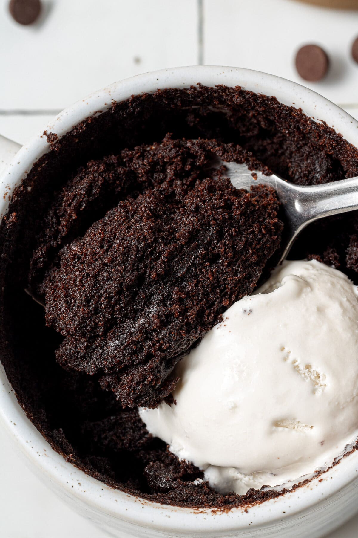 a vegan chocolate cake in a mug with a spoon and whipped cream on top