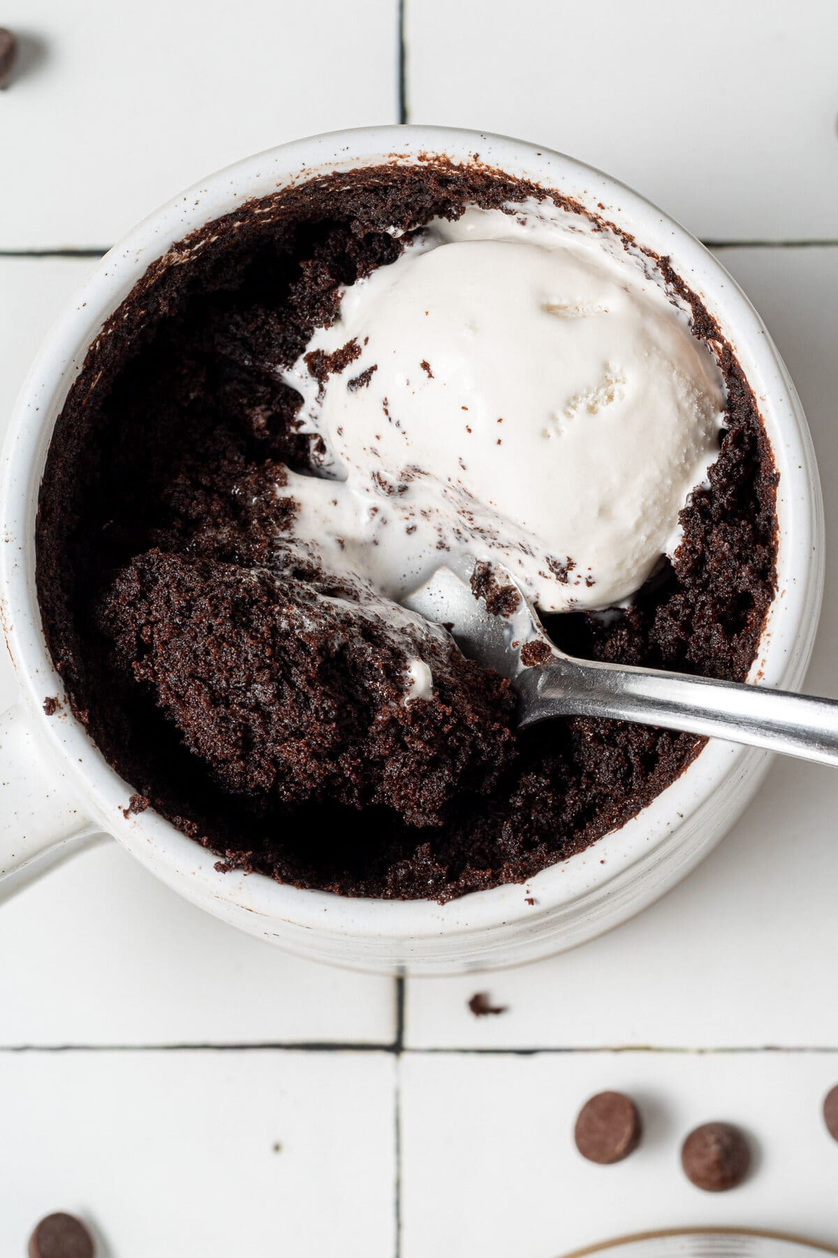 a vegan chocolate cake in a mug with a spoon and whipped cream on top with chocolate chips scattered around