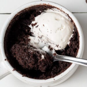 vegan mug cake with whipped cream on top and a spoon