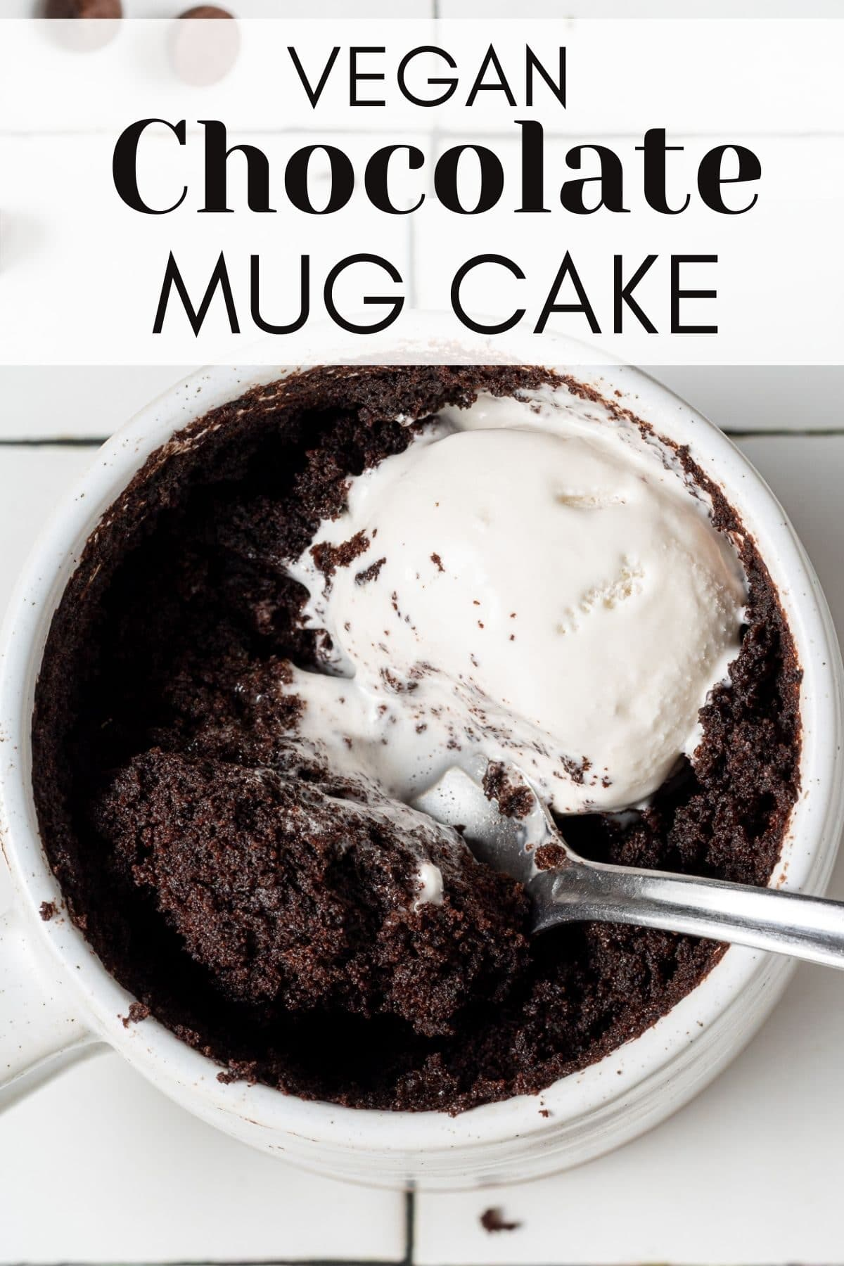 chocolate cake in a mug with vegan whipped cream on top and a spoon with text overlay