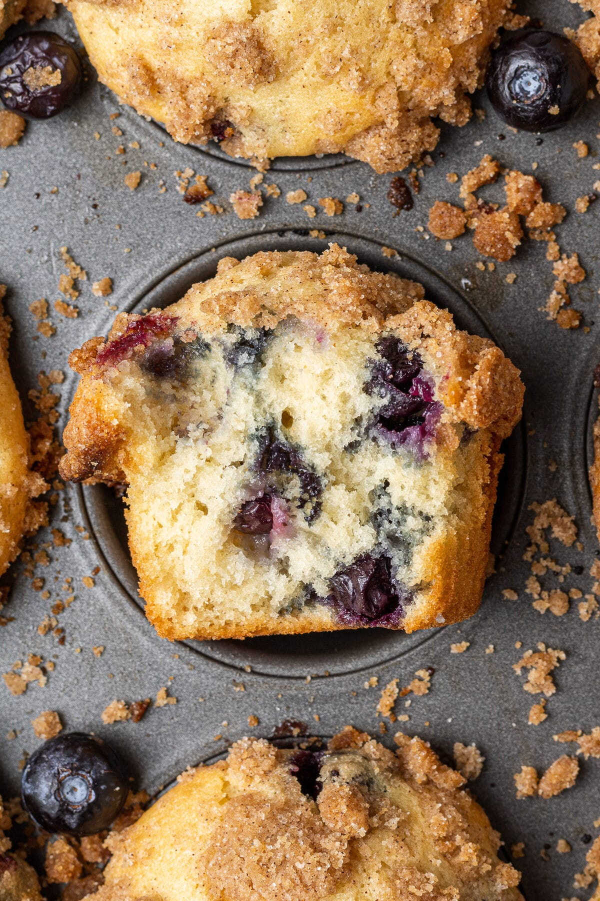 blueberry muffin in a pan with a bite out of it after being baked with blueberries scattered around them