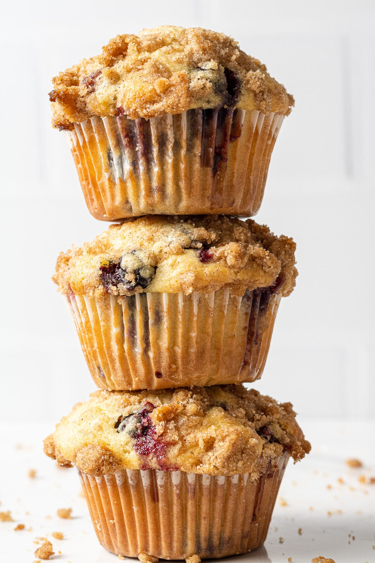 three dairy free blueberry muffins stacked on top of each other