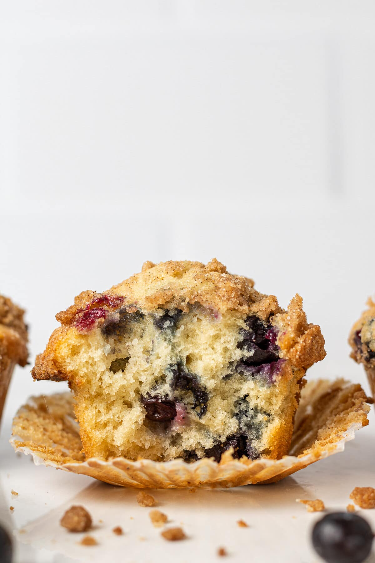 dairy free blueberry muffin with a bite out of it and crumbs around it