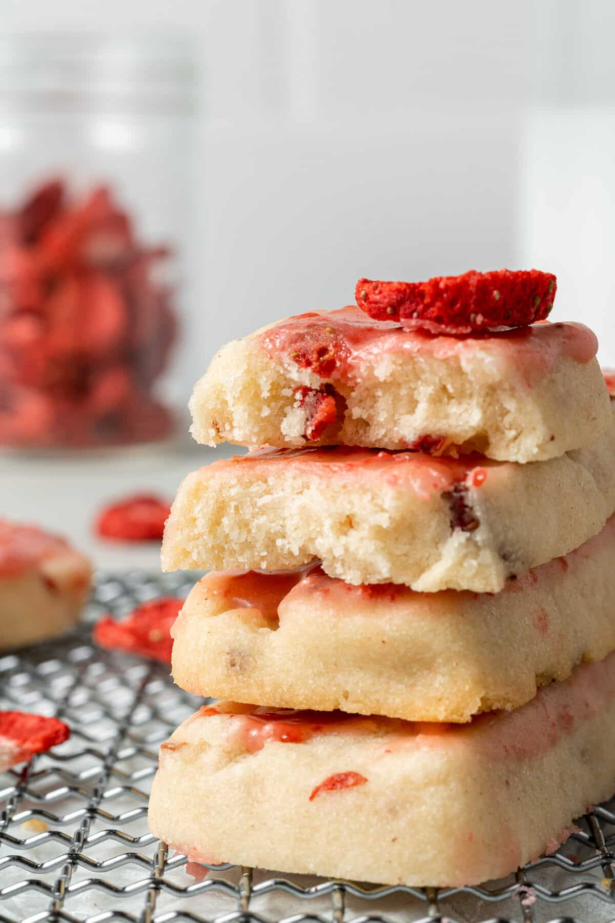 strawberry shortbread cookies stacked on top of each other with freeze dried strawberries in the background