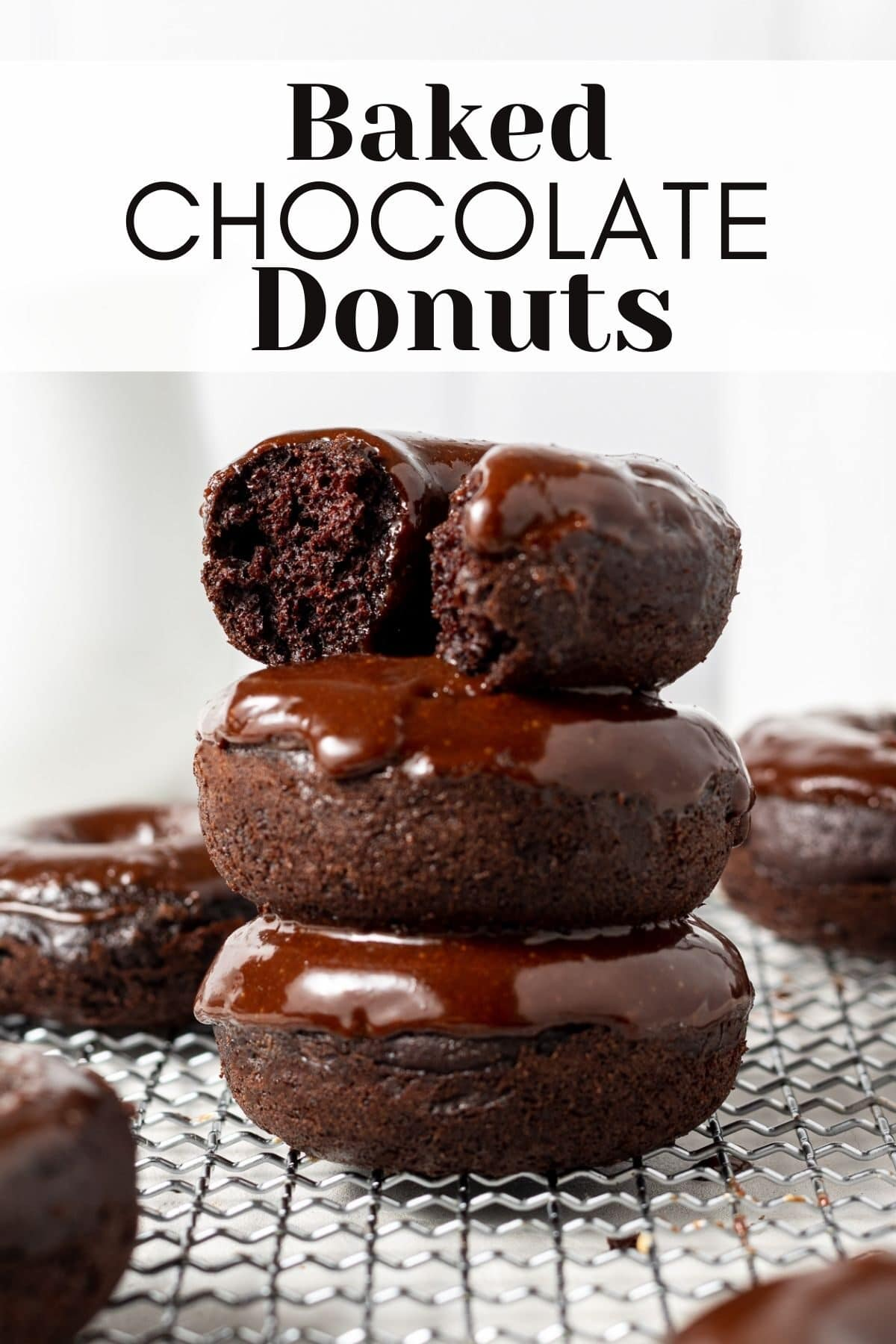 chocolate mini donuts stacked on top of each other with more donuts in the background and text overlay for pinterest