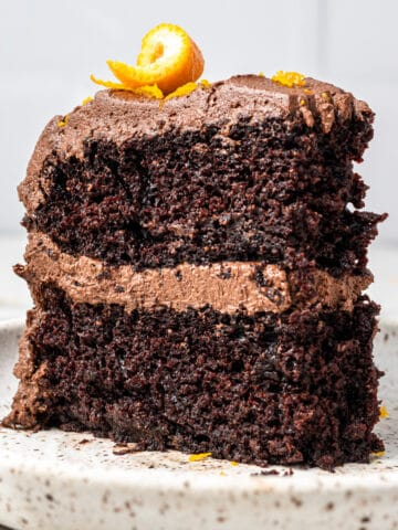 chocolate orange cake on a plate with orange twist on top