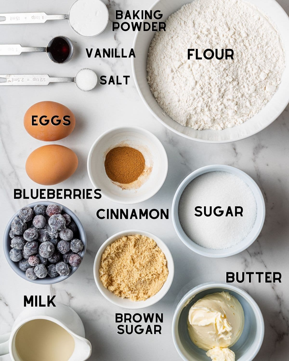 ingredients to make dairy free blueberry muffins in bowls labeled
