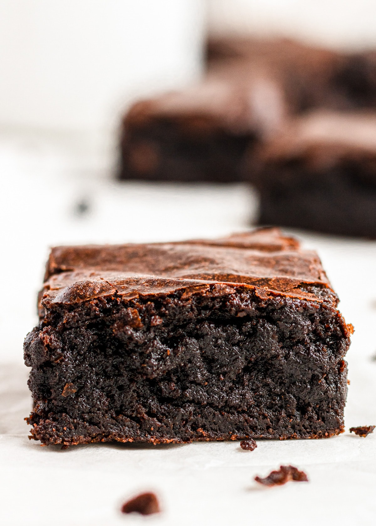 sliced dairy free fudgy brownie on parchemnt and more brownies in the background