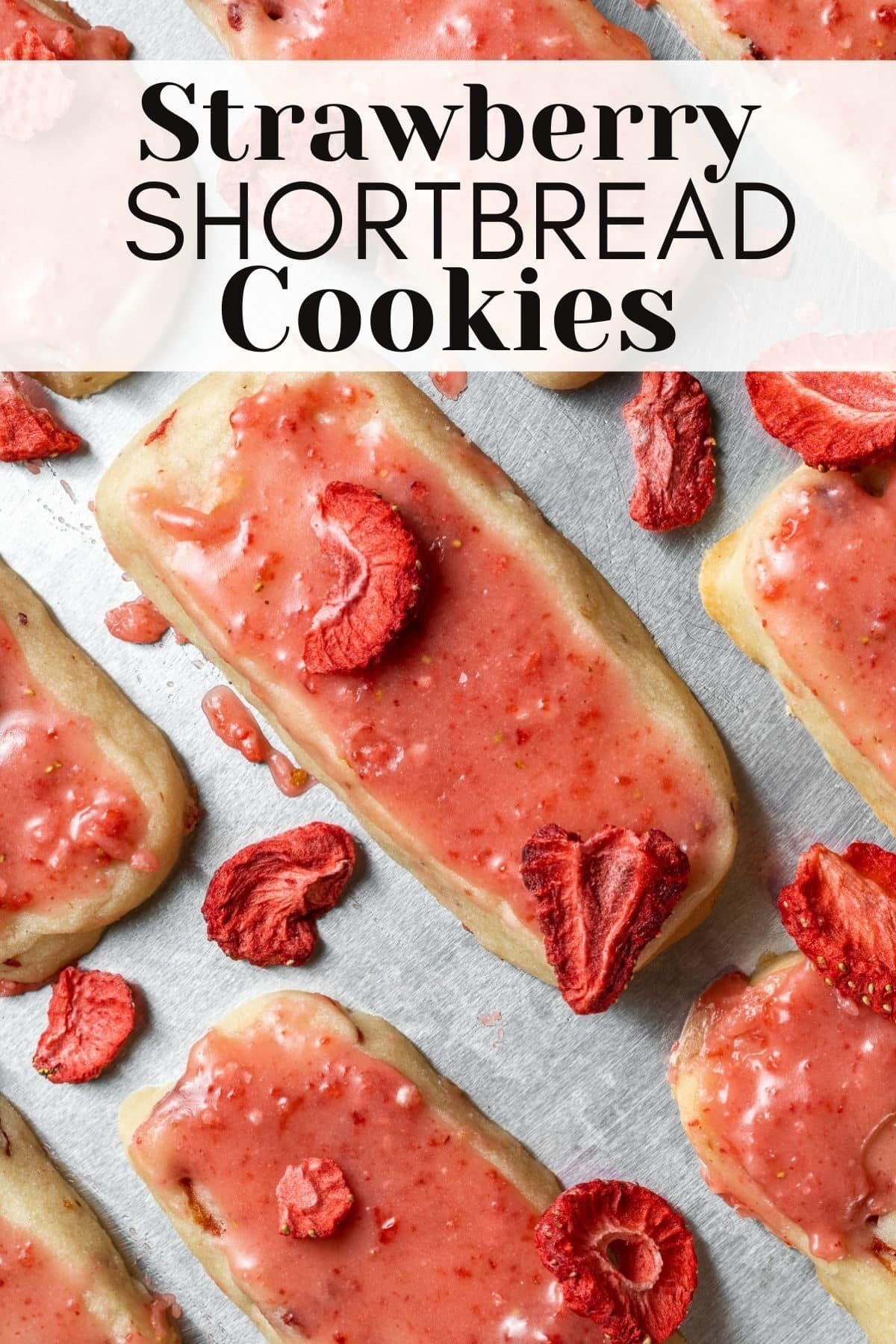 strawberry shortbread cookies on a baking tray with freeze dried strawberries round them and text overlay