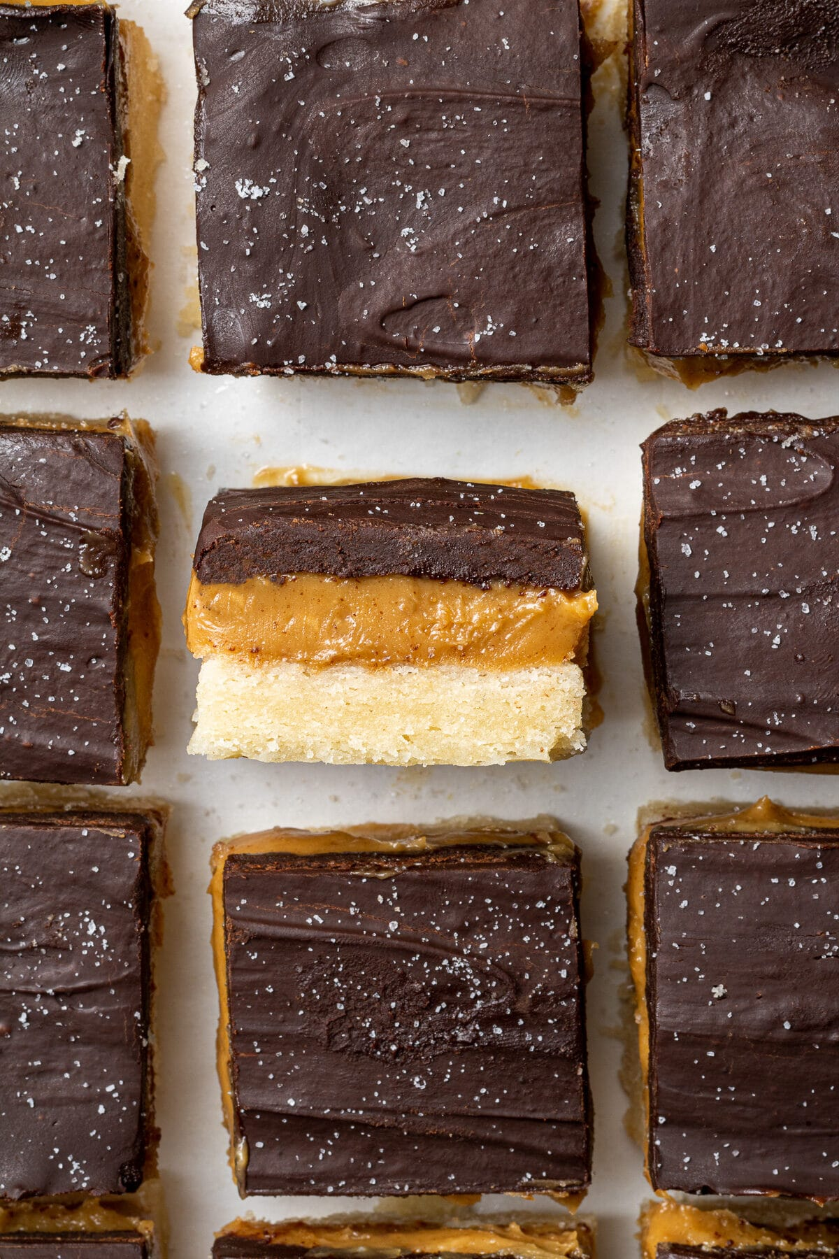 a vegan millionaire shortbread bar on it's side showing the layers surrounded by other millionaire bars