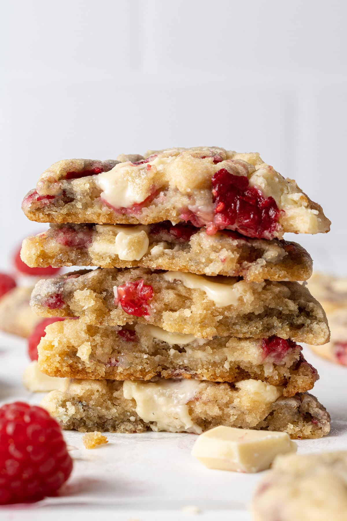 white chocolate and raspberry cookies stacked on top of each other and split in half with chunks of white chocolate and fresh raspberries scattered around