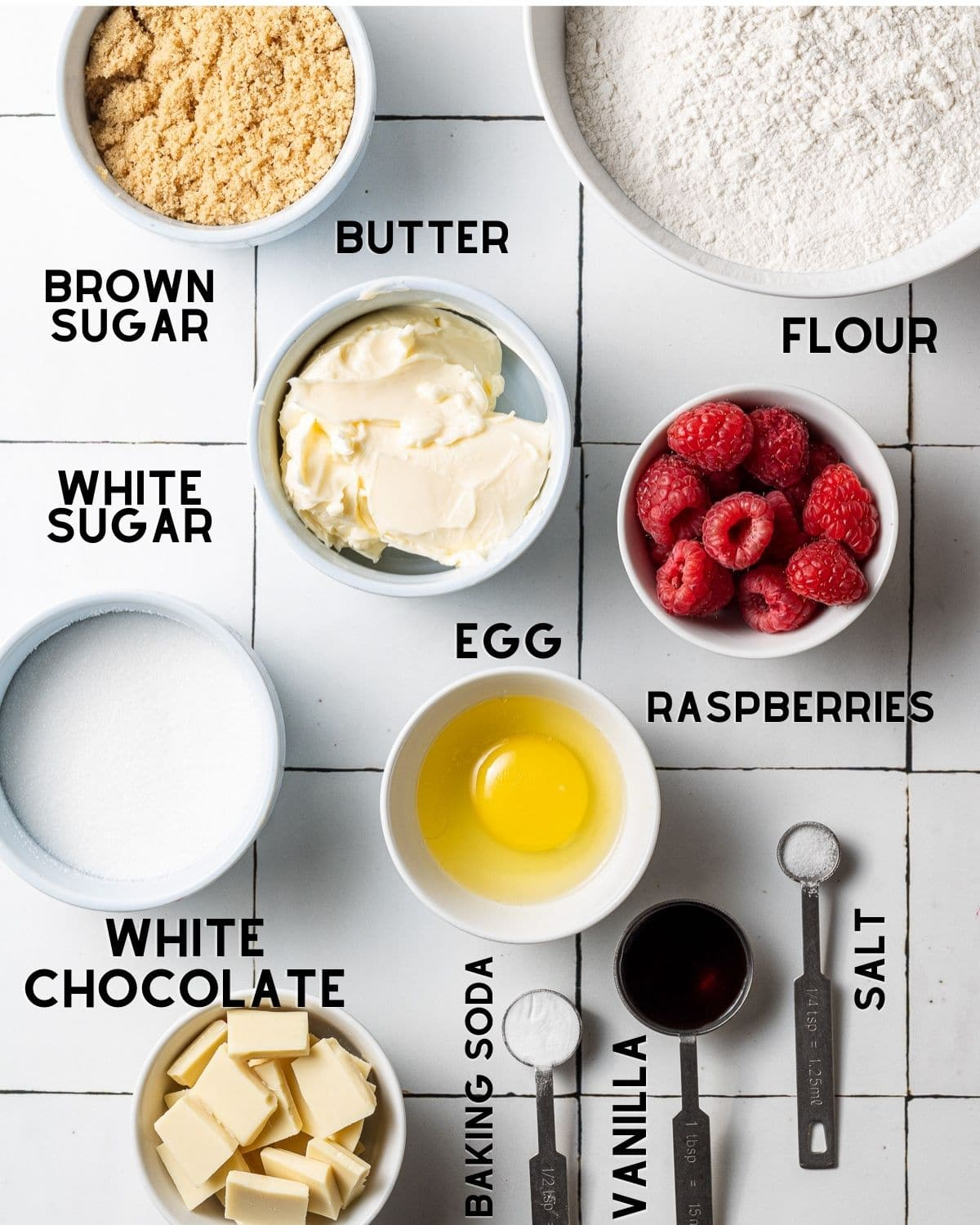 ingredients to make white chocolate and raspberry cookies in bowls with labels