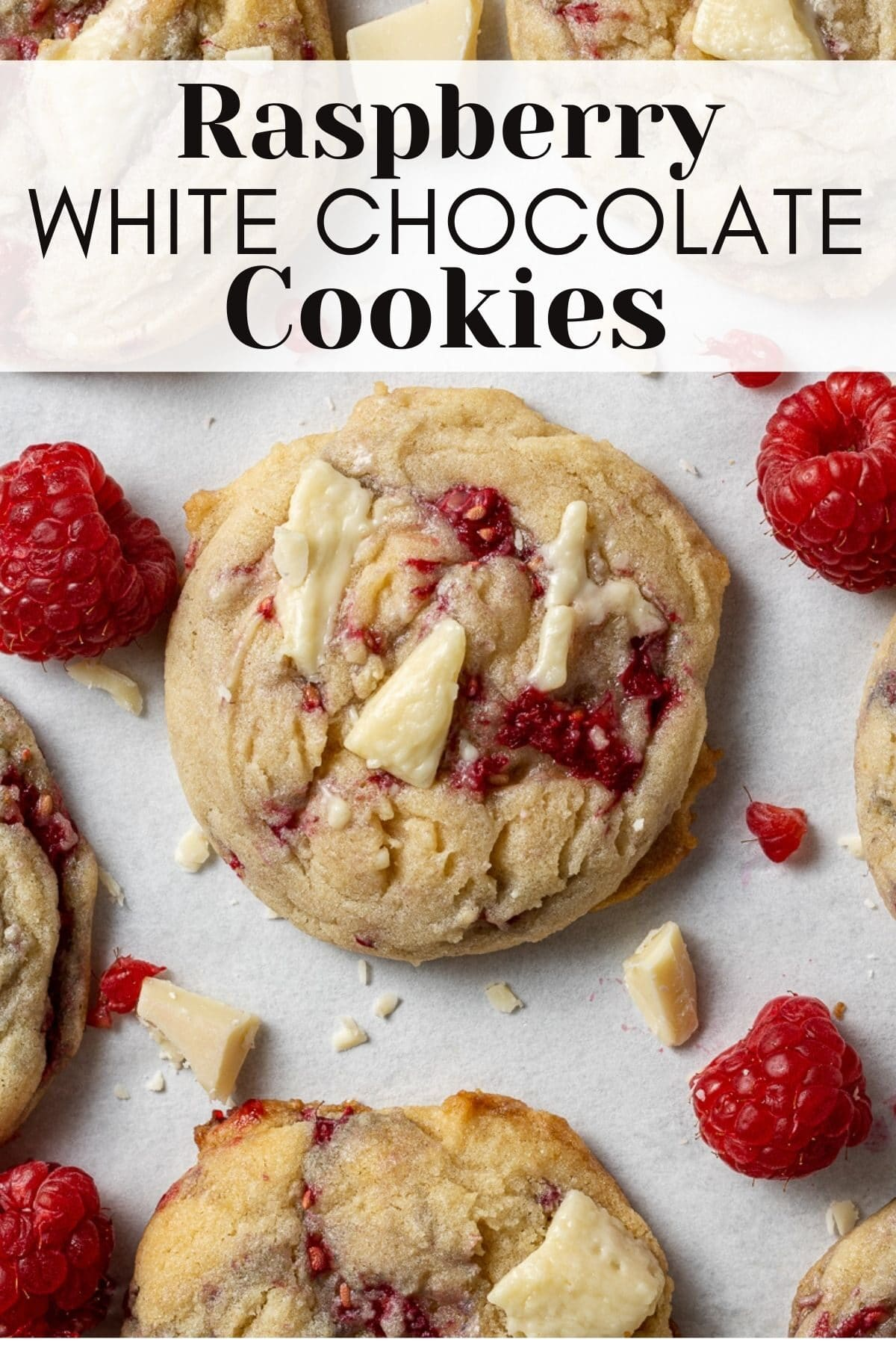 white chocolate and raspberry cookies on parchment with chunks of white chocolate and fresh raspberries scattered around with text overlay for pinterest