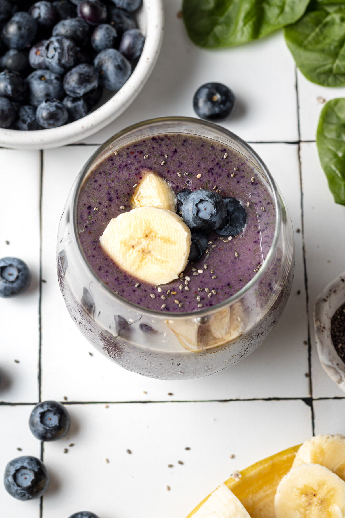 blueberry banana spinach smoothie in a glass with bananas and blueberries scattered around and chia seeds on top