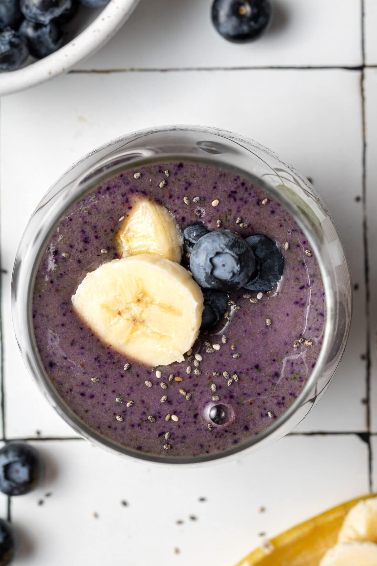 blueberry banana spinach smoothie in a glass with bananas and blueberries and spinach leaves scattered around and chia seeds on top