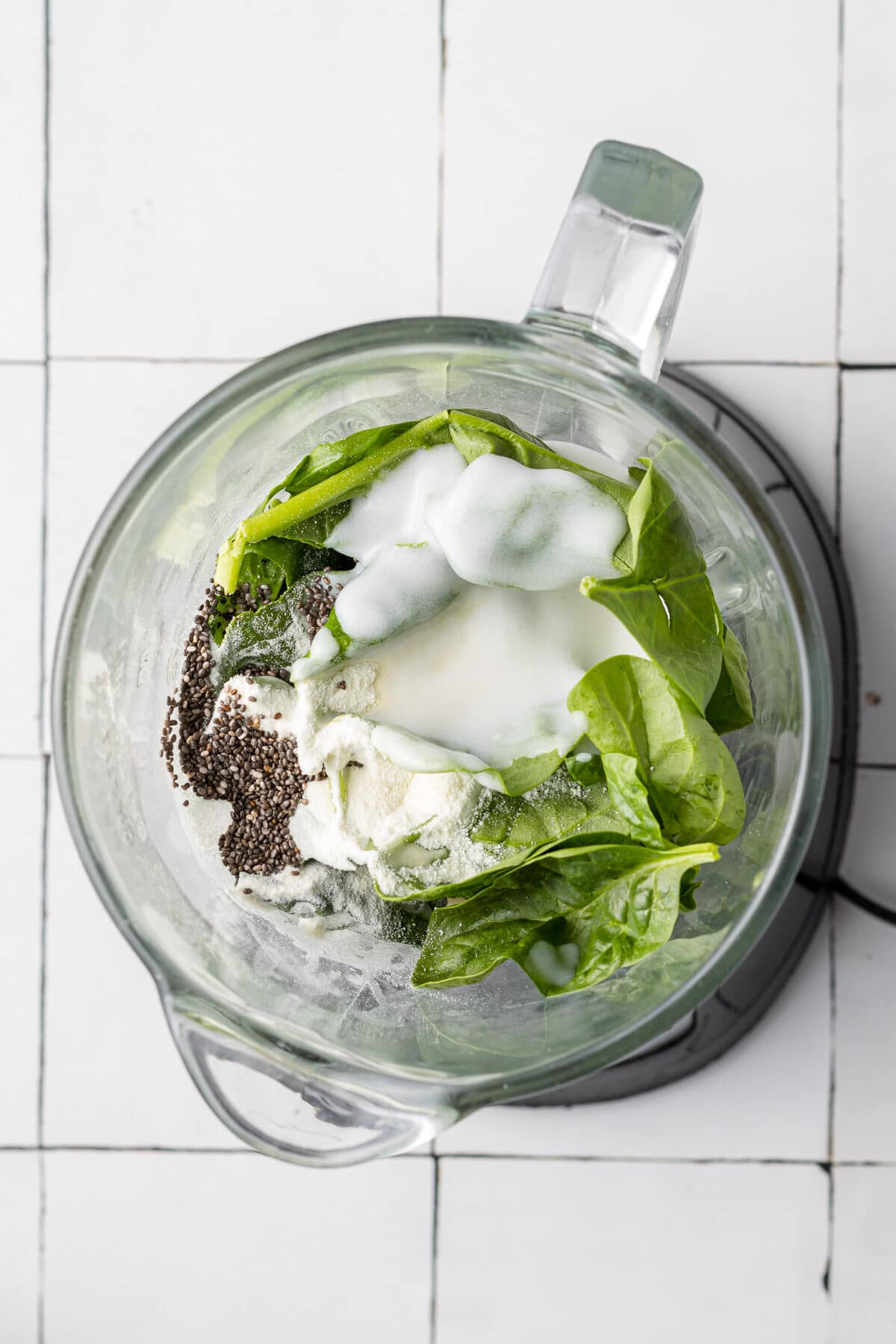 ingredients to make a blueberry banana spinach smoothie in a blender