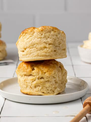 dairy free biscuits stacked on a plate with butter in the background
