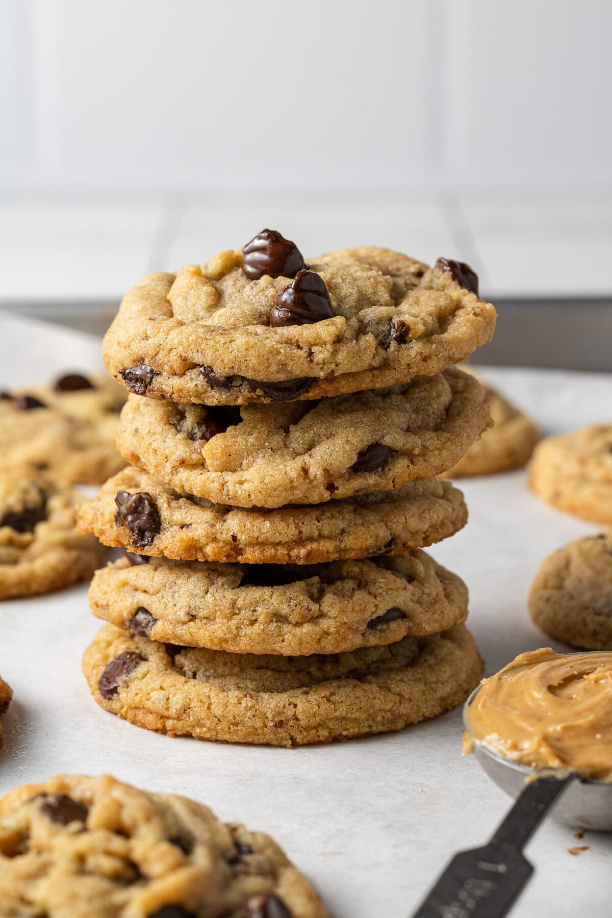 vegan peanut butter cookies stacked on each other with more cookies around them