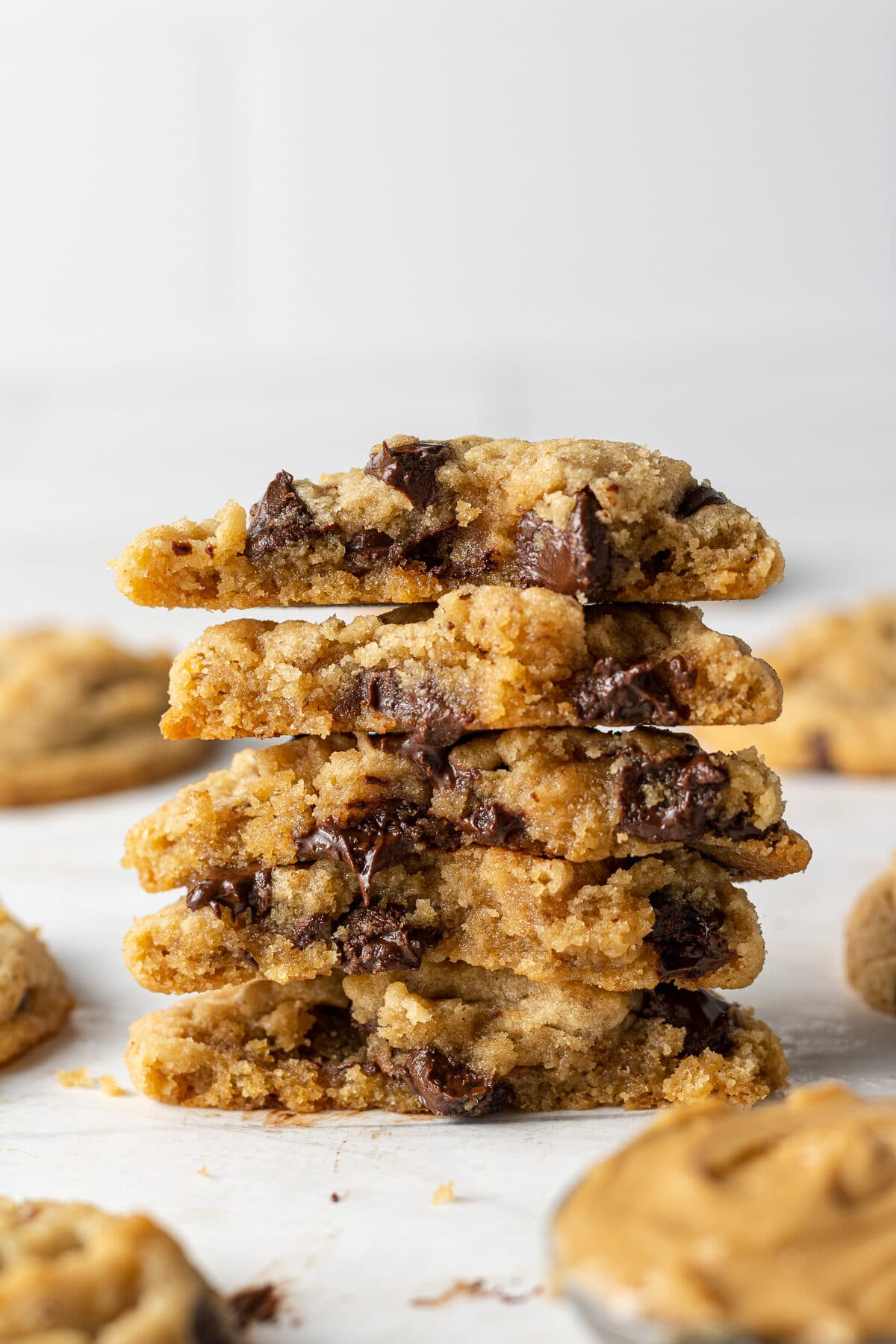 vegan peanut butter cookies split in half with more cookies around them
